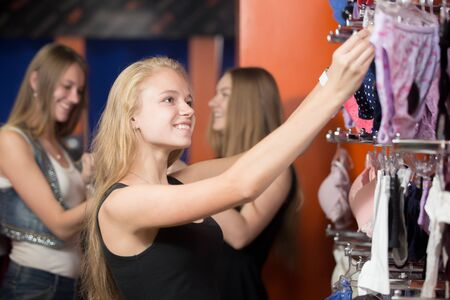 undies: Portrait of blond happy young beautiful woman shopping, standing in the mall, looking at hangers with lingerie, choosing new underwear in shop, group of cheerful friends chatting on the background Stock Photo