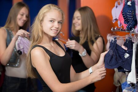 undies: Portrait of happy young beautiful blond woman shopping, standing in the mall, looking through hangers with lingerie, choosing new underwear in shop, friendly smiling at camera Stock Photo