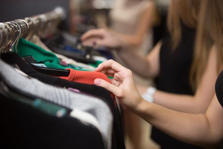 casual clothes: Hermosas mujeres j�venes de compras en el centro comercial de la moda, la elecci�n de la nueva ropa, mirando a trav�s de perchas con diferentes prendas de colores casuales en perchas, cerca de las manos