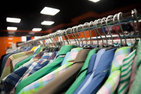 shirts on hangers: Hangers with colorful male shirts in fashion mall, close up
