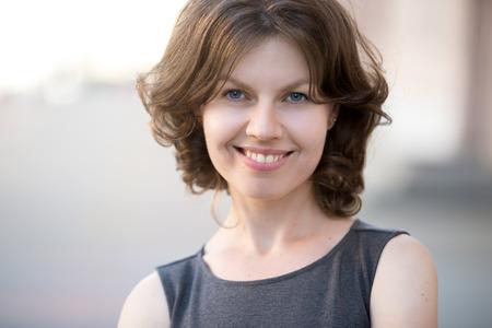 mujer elegante: Retrato de mujer feliz de negocios hermosa posando en la calle en verano, amable y sonriente, mirando a la c�mara con alegre expresi�n de confianza