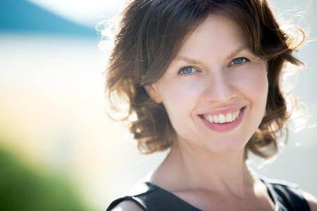 Headshot Portrait der glücklichen schönen kaukasischen Frau auf der Straße im Sommer, freundlich lächelnd, Blick in die Kamera mit fröhlichen zuversichtlich Ausdruck