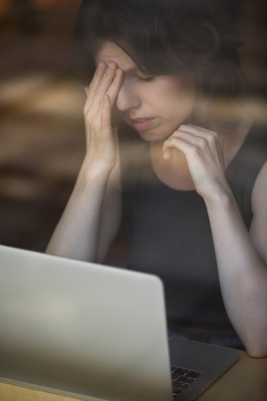 high blood pressure: Young woman sitting in cafe in front of laptop, leaning on her hand, touching head with tired expression, having headache, low or high arterial blood pressure, stress Stock Photo
