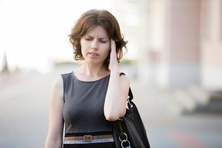 confundido: Retrato de joven mujer de la oficina caminando en la calle en verano, con el ceño fruncido con subrayado, la expresión facial confundido, sosteniendo su cabeza con la mano tratando de recordar algo