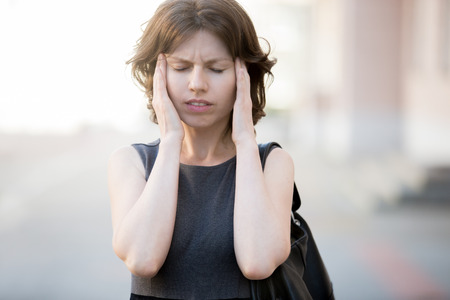 Portrait of young woman walking on the street in summer, frowning, holding her head in hands, having headache, low or high arterial blood pressure, stress Stock Photo