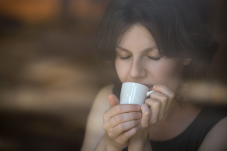 interior shot: Portrait of beautiful happy smiling young woman sitting in modern cafe holding cup of coffee, enjoying her drink with eyes shut, interior shot through window glass