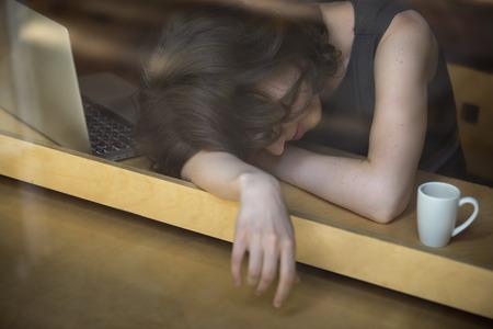 agotado: Joven acostado en los brazos sobre la mesa en el café delante de la computadora portátil con la taza de café, soñoliento, cansado, con exceso de trabajo o perezoso a trabajar temprano en la mañana