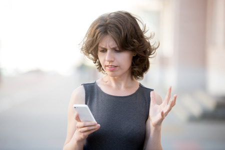 Portrait of young woman holding cellphone in hands on the street in summer, looking at screen with irritated expression, made a mistake or annoyed by texts and calls