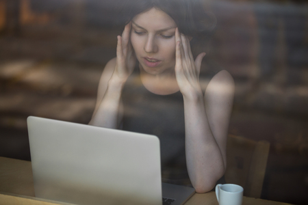 Young woman sitting in cafe in front of laptop, looking at screen with frustrated expression, holding her head in hands, having headache, low or high arterial blood pressure, stress