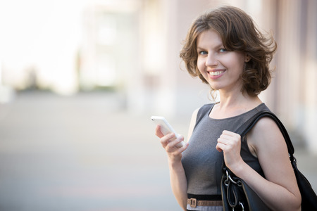 Portrait of happy office woman with leather bag holding cellphone in hands on summer street, using app, messaging, friendly smiling, looking at camera with cheerful expression, copy space 스톡 콘텐츠