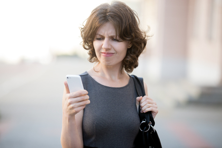 stressed business woman: Portrait of stressed office young woman holding cellphone in hands on the city street in summer, looking at screen with cross face expression, mad at stressful texts and calls