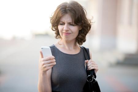 Retrato de oficina estresado mujer joven que sostiene el teléfono móvil en las manos sobre la calle de la ciudad en verano, mirando la pantalla con la expresión de la cara cruz, enojado con textos estresantes y llamadas Foto de archivo - 46075254