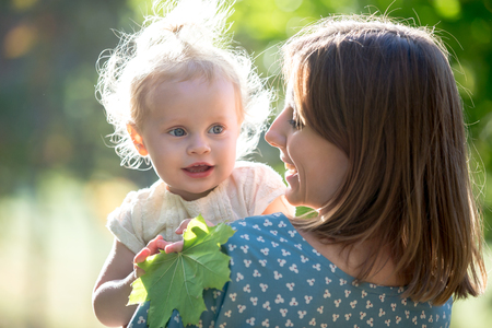 citypark: Portrait of happy young mom and adorable blond baby girl, smiling mother holding her little daughter in arms, talking, playing with tree leaf, walking together in park in sunny weather Stock Photo