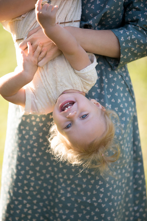 tot: Young mom and cheerful adorable blond tot girl playing, having fun together in park in summertime, mother playfully holding her cute little daughter upside down, close up Stock Photo