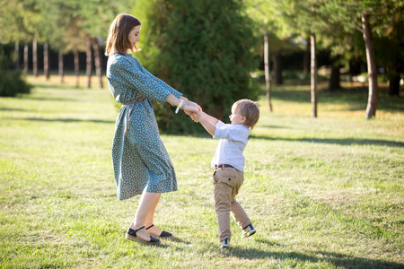 Portrait of happy young mom and her adorable little son playing and dancing together in park in summertime, smiling mother and kid holding hands, spinning, having fun together, full length