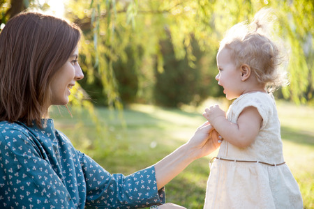 Happy young mom and adorable blond girl playing together in park in summertime, smiling mother holding her little daughter hand, supporting her first steps, looking at baby with adoration