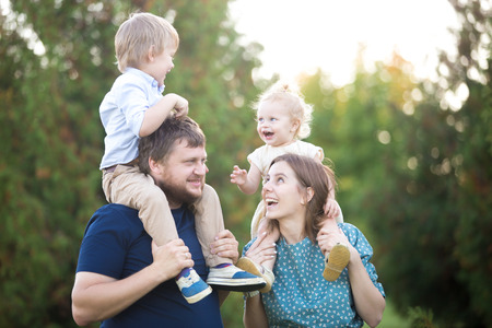 Portrait of happy beautiful family of four walking in park in summer. Mom and dad carrying two little cheerful laughing kids on shoulders. Parents and siblings playing, having fun together Stock Photo