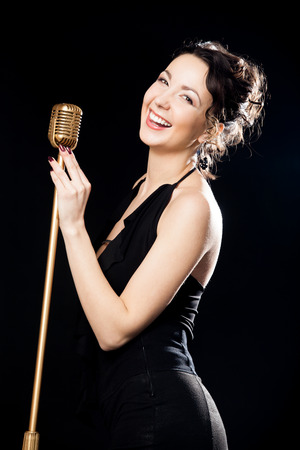 vocalist: Beautiful young female vocalist in black evening dress happily laughing holding golden retro microphone, on the stage during live musical performance Stock Photo
