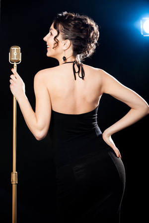 black professional: Beautiful young female vocalist in black sexy evening dress holding golden vintage microphone, playful smile, standing on stage lit by blue scenery projector