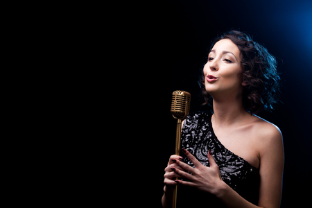 singing: Beautiful young female vocalist in shiny black evening dress singing with emotions behind golden retro microphone, during live musical show, copy space Stock Photo
