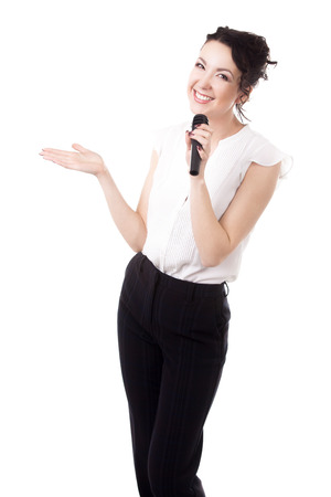 Presentation, public speech, conference, sales, advertising. Young businesswoman, reporter, media presenter holding microphone, pointing on copy space, isolated