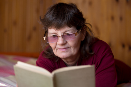 shortsighted: Cute senior woman in glasses reading a book, lying comfortable on bed at home in cozy rural room with wooden walls, enjoying poetry, engrossed in interesting story plot