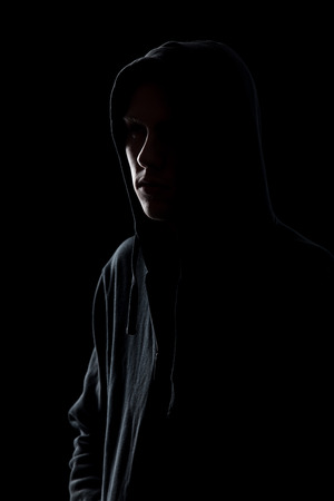 Silhouette of dimly lit man in hooded sweatshirt, dangerous unrecognizable stranger, criminal