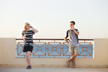 Minimalistic portrait of young happy smiling couple, man and woman holding cellphones, talking on mobile phones, standing in relaxed poses on sunny summer terrace with sea scenery Stock Photo