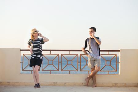 Minimalistisch-Porträt der jungen glücklich lächelnde Paar, Mann und Frau, die Handys, sprechen auf dem Handy, stehend im entspannten Posen an sonnigen Sommerterrasse mit Meerlandschaft Standard-Bild - 46507052