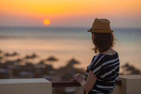 puesta de sol: Mujer joven en el sombrero y vestido lindo del verano de pie en la terraza con un paisaje de mar tranquila, mirando al atardecer o un amanecer en el horizonte, vista posterior, espacio de copia
