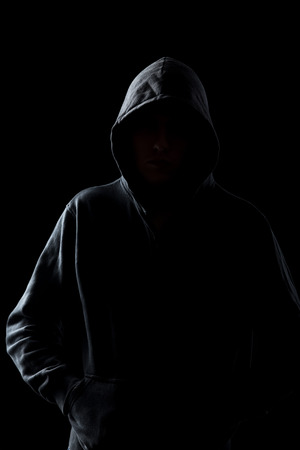 Silhouet van anonieme man in hoodie in de duisternis, concepten van gevaar, misdaad, terrorisme