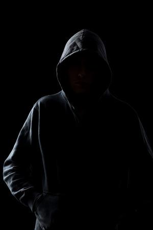 Sylwetka anonimowego faceta w bluzy w ciemności, koncepcje niebezpieczeństwa zbrodni, terroru