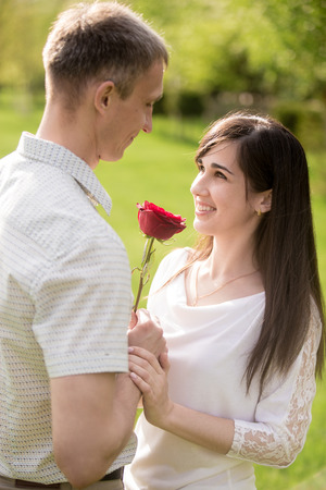 confessing: Couple of lovers meeting on a date, looking in each other eyes, young man giving red rose to his beautiful happy smiling brunet girlfriend