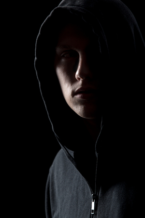 hoodlum: Portrait of mysterious man in hoodie in the dark, dangerous criminal scarcely visible in the dusk Stock Photo