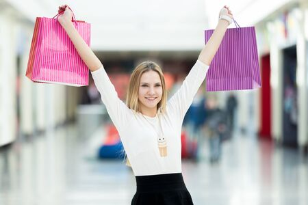 profitable: Excited young woman enjoy shopping, holding up shopping bags with joy. Sale, discount, fashion, profitable offer concepts Stock Photo