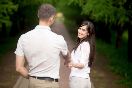 giggling: Young brunette woman in casual clothes leading by hand her boyfriend, inviting him for a walk in park, playfully looking at him, giggling, follow me concept Stock Photo