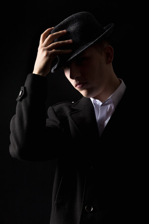 mafioso: Handsome unrecognizable elegant mafioso man in coat touching his hat as in greeting, scarcely visible in the darkness