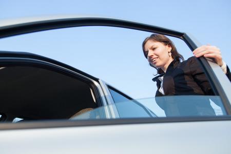 abrir puertas: Tiro sincero de puerta de apertura mujer de su coche antes de entrar, listo para un paseo