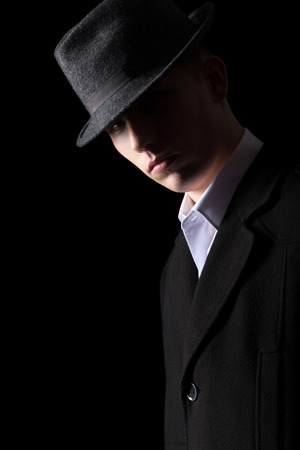 low key lighting: Handsome brutal looking man in coat and hat in the darkness, studio shot against black background, low key lighting Stock Photo