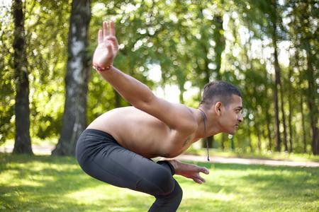 padma: Sporty handsome Indian young man working out in park, preparing for Half Lotus Tip Toe Pose, Ardha Baddha Padma Padangusthasana, Padangustha Padma Utkatasana, side view