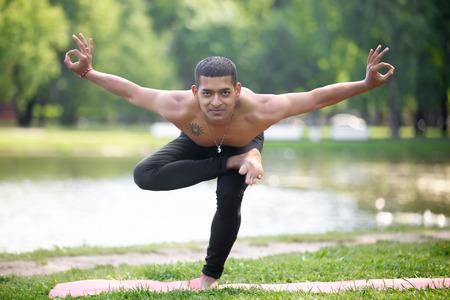 ardha: Attractive smiling asian young man working out in park, preparing for Half Lotus Tip Toe Pose, Ardha Baddha Padma Padangusthasana, Padangustha Padma Utkatasana, full length, front view