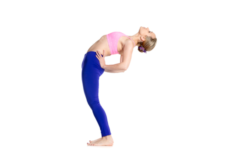to bend: Sporty beautiful young blond woman doing Standing Backward Bend yoga posture, Ardha Chakrasana, Half Wheel pose, studio full length isolated shot on white background, side view Stock Photo