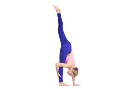 eka: Sporty beautiful young blond woman in purple leggings doing Standing Split yoga pose, Urdhva Prasarita Eka Padasana, studio full length isolated shot on white background, profile view