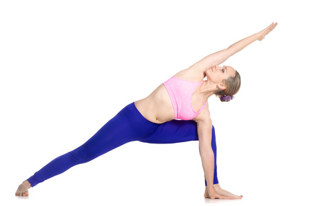 parsvakonasana: Sporty beautiful young blond woman doing lunge exercise, standing in Extended Side Angle posture, studio full length isolated shot, profile view on white background, part of large photo series