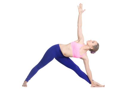 trikonasana: Sporty beautiful young blond woman doing Utthita Trikonasana posture, Extended Triangle Pose, studio full length isolated shot, profile view on white background Stock Photo