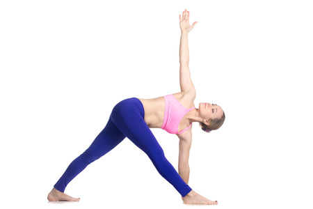 Sporty attractive young blond woman doing side bend, Parivrtta Trikonasana posture, Revolved Triangle Pose, studio full length isolated shot, profile view on white background