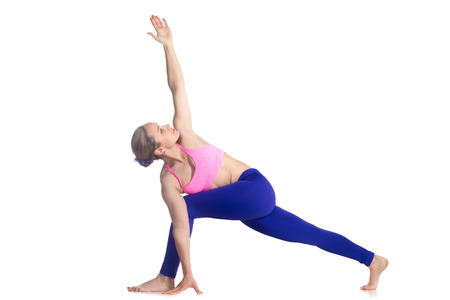 side angle pose: Sporty attractive young blond woman doing Revolved Side Angle Pose, parivritta parshvakonasana posture, studio full length isolated shot, profile view on white background