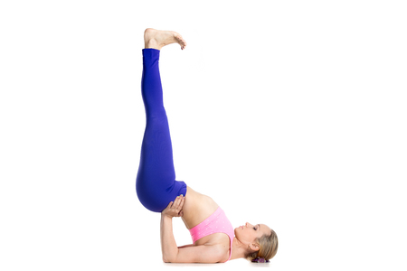 supported: Sporty beautiful young blond woman doing variation of shoulder stand exercise, Viparita Karani, Upside-Down Seal pose, studio full length isolated shot, profile view on white background Stock Photo