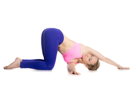 thread: Sporty beautiful young blond woman doing kneeling twist parivrtta marjaryasana, threading the needle, warming up shoulders, studio full length isolated shot, side view on white background