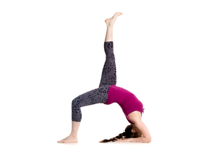 pada: Sporty beautiful young woman doing one legged variation of Bridge Pose, eka pada urdhva dhanurasana (Upward Bow), Chakrasana (Wheel) posture, studio full length isolated shot on white background